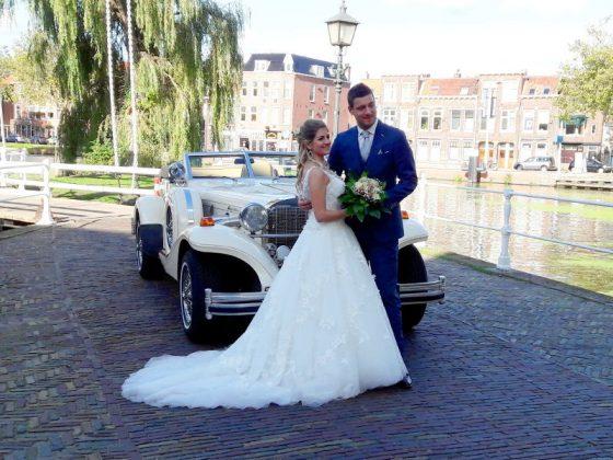 Bruidspaar met een klassieke trouwauto